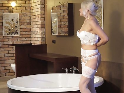 Mouthwatering GILF Sylvie takes off sexy lingerie and masturbates in the bathtub